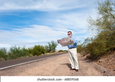 A lost man stands alone on a deserted road reading a map.