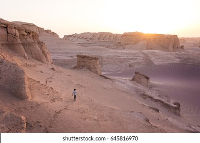 A lost man wandering through pink desert sands at sunrise as the sun breaks over a sand rock formation in the Lut desert in Balochistan in southern Iran