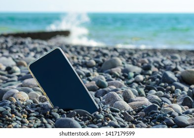 lost mobile phone is located among the sea pebbles on the background of the sea