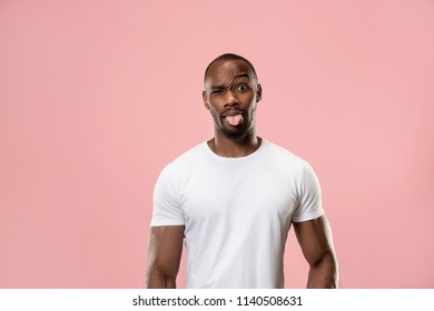 I lost my mind. The squint eyed man with weird expression. Beautiful male half-length portrait isolated on pink backgroud. The crazy man. The human emotions, facial expression concept.