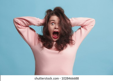 I lost my mind. Stress. The screaming woman with horror expression. Beautiful female half-length portrait isolated on blue studio backgroud. The crazy woman. The human emotions, facial expression