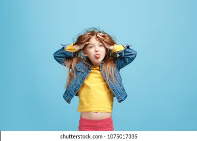 I lost my mind. The teen girl with weird expression. Beautiful female half-length portrait isolated on blue studio backgroud. The crazy teenager. The human emotions, April fools day