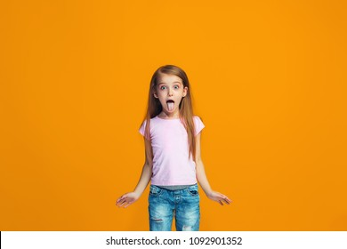 I lost my mind. The teen girl with weird expression. Beautiful female half-length portrait isolated on orange studio backgroud. The crazy teenager. The human emotions, facial expression concept.