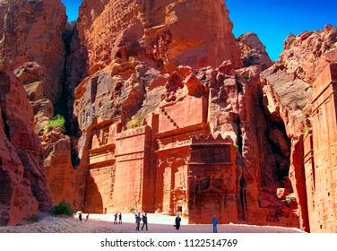 The lost nabatean city Petra, Jordan, Middle East, Western Asia. Awesome scenic view - gorge in the midds of huge steep red rocks, ancient stone carved tombs and few walking people
