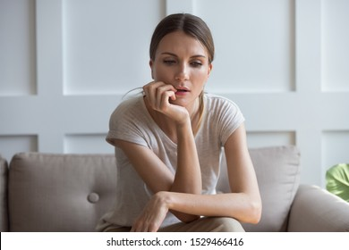 Lost on sad thoughts millennial 30s woman sitting on couch at home feels emptiness by personal difficulties and unsolvable problems, concept of jealous wife, lonely single frustrated female concept