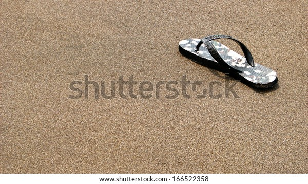 Lost Pair of Flip Flops Sandals on Sandy Beach