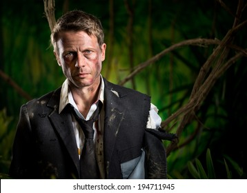 Lost scared businessman standing in the jungle in torn dirty clothing.