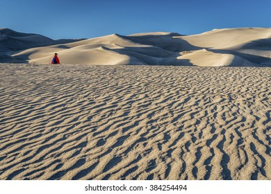 Lost in the sea of sand -  a lonely hiker in a dunefield in Great Sand Dunes National Park, Colorado