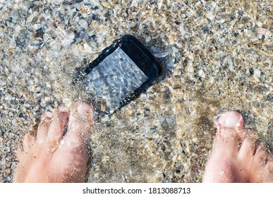 Lost smartphone underwater at sea. Losing phone the beach, concept image.