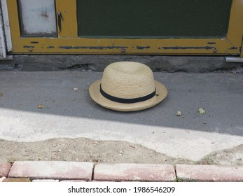 a lost straw hat with a black ribbon laying on a sidewalk