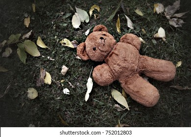 Lost teddy bear laying on the ground