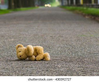 Lost teddy bear lying alone on the road