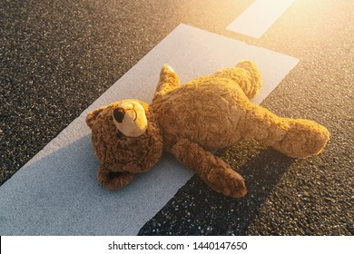 Lost teddy bear lying on the street after an accident