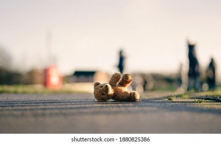 Lost Teddy bear with sad face lying on footpath with blurry people ,Lonely bear doll laying down on the brick floor in gloomy day, Lost toy or Loneliness concept, International missing Children