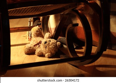 Lost teddy bear under rocking chair