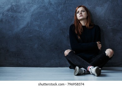 Lost teenage girl sitting on the floor against dark background with copy space