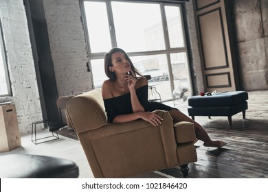 Lost in thoughts. Attractive young woman in elegant black dress looking away and keeping hand on chin while sitting on the sofa