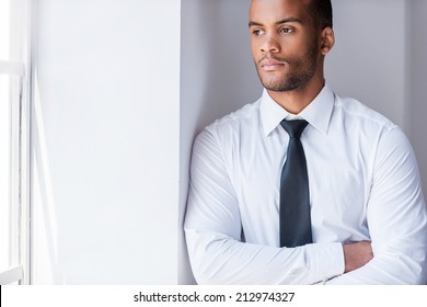 Lost in thoughts. Handsome young African man in shirt and tie looking through the window and keeping arms crossed while leaning at the wall