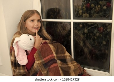 Lost in thoughts. Little child relax on Christmas eve. Small child with bunny toy at window. Small girl hold toy friend. Little girl enjoy Christmas spirit at home. Merry Christmas and happy new year.