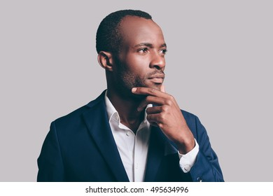 Lost in thoughts. Portrait of thoughtful young African man in smart casual jacket holding hand on chin and looking away while standing against grey background