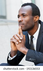 Lost in thoughts. Thoughtful young African man in formal wear keeping hands clasped and looking away while sitting outdoors
