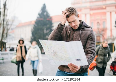 Lost tourist looking at city map on a trip. Looking for directions.