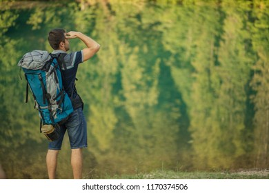 lost traveler with backpack is looking for the way. back view photo. tourism, travel, holiday, vacation concept. copyspace. breathtaking nature on the background of the phot