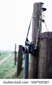 Lost vintage SLR camera hanging on fence post in countryside.
