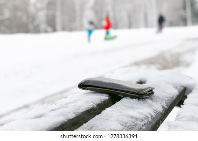 Lost wallet is forgotten by person on a bench in a winter park.