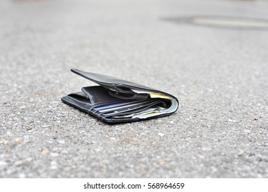 Lost wallet with money and credit cards is lying on pavement in city