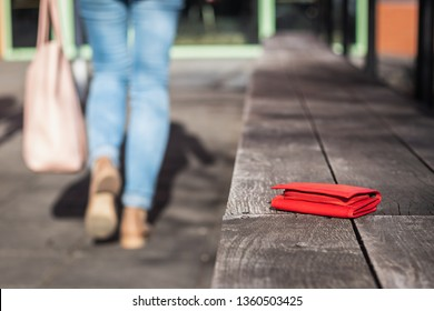 Lost wallet on city street. Woman is leaving from a bench where she forgot her leather wallet