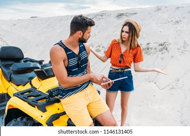 lost young couple with ATV using digital tablet in desert