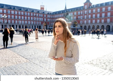 Lost young tourist woman checking smart mobile phone trying to find directions. Looking worried and thoughtful consulting the cellphone app. In tourism in Europe, Spain, Madrid and technology concept.