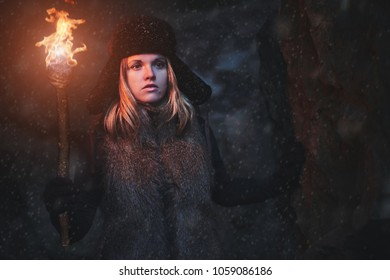 Lost young woman in with a torchlight at snowstorm