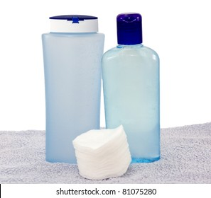 Lotions for the face and cotton pads on a towel
