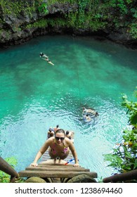 Lotofaga / Samoa - 04 11 2017: young caucasian woman standing on the ladder to turquoise water of famous To Sua Ocean Trench, natural wonder of Samoa on Upolu island, South Pacific, Oceania