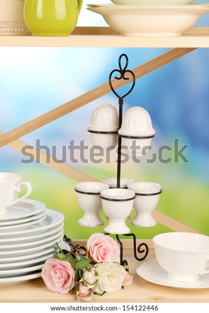 Lots beautiful dishes on wooden shelf on natural background