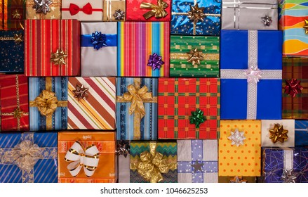 Lots of beautiful wrapped presents with bows tightly arranged, forming a colorful background