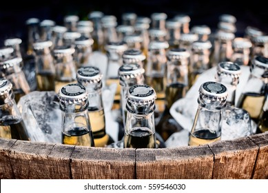 Lots of bottled craft beers in ice in an open barrel
