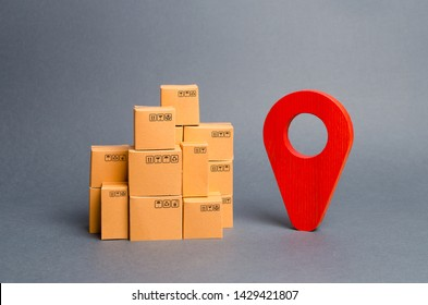 Lots of cardboard boxes and a red position pin. Locating packages and goods. Tracking parcels by the Internet. Algorithm for constructing a minimum route for the delivery of orders. World Trade
