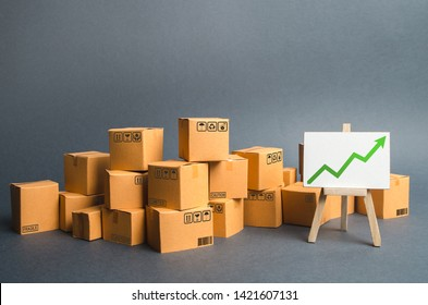 Lots of cardboard boxes and a stand with a green up arrow. rate growth of production of goods and products, increasing economic indicators. Increasing consumer demand, increasing exports or imports.