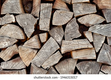 Lots of chopped firewood on a pile close up. Harvesting firewood for the winter. Dry firewood for a fireplace. Decorative wall from firewood.
