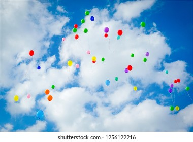 Lots of colorful balloons flying on cloudy blue sky