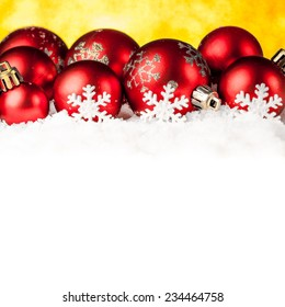 Lots of colorful Christmas Decoration baubles in snow on golden background