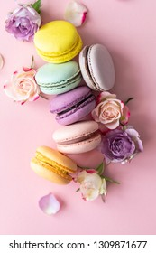 lots of colorful French macaroons and flowers on a pink background.