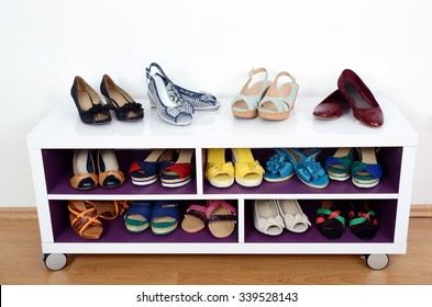 Lots of colorful summer shoes on a shelf. Shoes and sandals nicely arranged on a shelf
