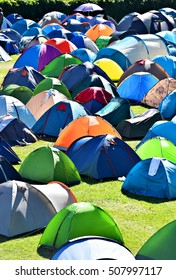 Lots of colorful tents on a meadow in a summer day during music festival
