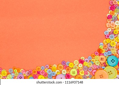 Lots of colourful buttons on an orange textured paper background with blank copy space.
