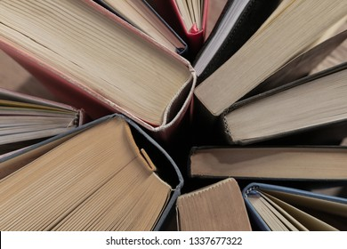 Lots of colourful thick open books stand on a dark background