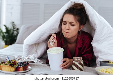 Lots of desserts. Heartbroken woman eating a lot of desserts because of depression and huge stress at work